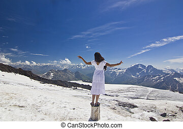 girl in white dress standing on snow slope with hands-up in mountains