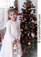 Girl in white dress with lantern under Christmas tree