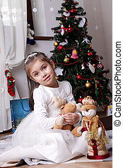 Girl in white dress with snowman under Christmas tree