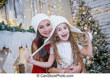 Girl in white hat with mother under Christmas tree