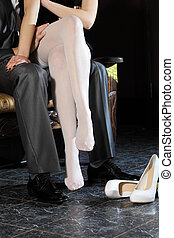 girl in white stockings seduces man indoors. Embrace the men...