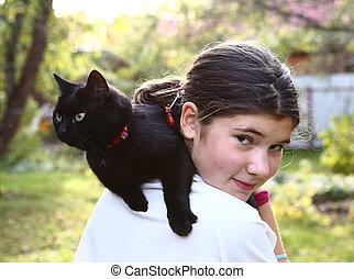 girl in white t-shirt hold black cat on shoulder