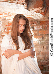 Girl in white tissue near brick wal