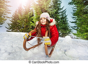 Girl in winter clothes having fun on snow sledge