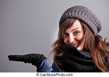 girl in winter clothes showing off COPY SPACE