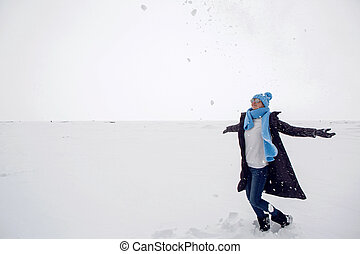 girl in winter clothes standing on a frozen lake