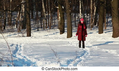 girl in winter forest runs through snow