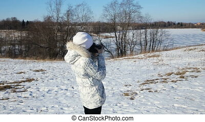 Girl in winter park with camera photographs.