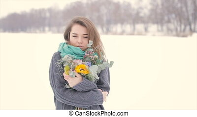 Girl in winter with a bouquet of flowers in hands.Slow motion