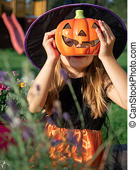 Girl in witch costume hiding behind artificial pumpkin