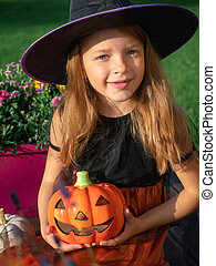 Girl in witch costume holding artificial pumpkin