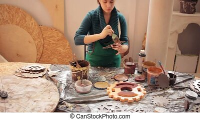 Girl in workshop painting wooden items - Young concentrated...
