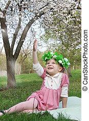 Girl in wreath having fun under tree