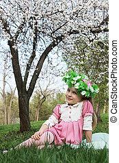 Girl in wreath sitting under spring tree