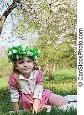 Girl in wreath under spring tree