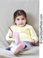 Girl in yellow with pencil