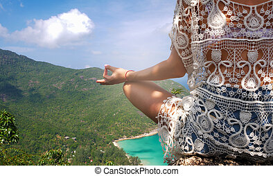 girl in yoga pose with picturesque view of the island at a height