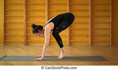 Girl indoors in retreat space doing handstand pose. Strong...