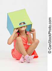Girl indulging in a box for toys put on the head