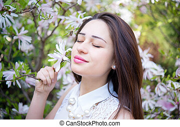 girl inhales the aroma of blooming magnolias