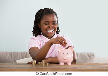 Girl Inserting Coins In Piggy Bank - Portrait Of An African...