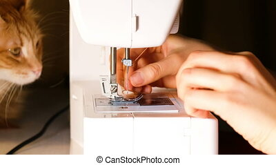 Girl inserts a thread a needle on a sewing machine, a cat silit on the table
