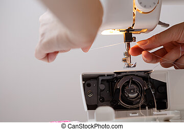 Girl inserts thread in sewing-machine - Girl inserts thread...