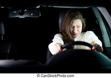 girl is afraid holding the steering wheel
