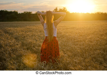 Girl is back in a wheat field with his hands behind his head