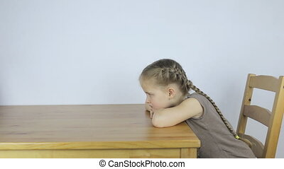 Girl is bored alone, sitting at the table - Little girl is...