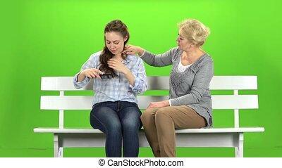 Girl is combing her hair. Green screen