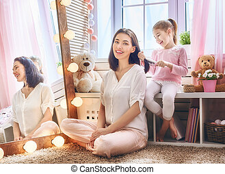 girl is combing her mother's hair - Happy loving family....