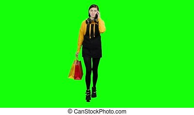 Girl is coming with packages and talking on the phone. Green screen