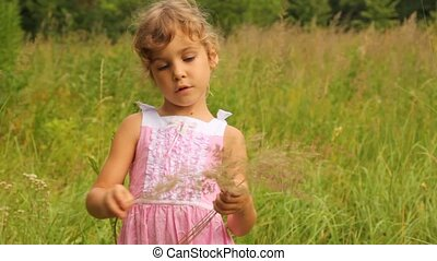 girl is counting the blades of grass which she has gathered...