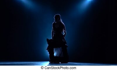 Girl is dancing a sexy dance in a dark room. Llight from behind. Smoke background. Silhouette