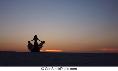 Girl is dancing belly dancing against the beautiful sunset on the beach. Silhouettes