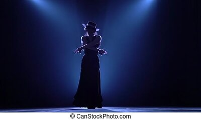 Girl is dancing castanets in her hands dancing. Llight from behind. Smoke background. Silhouette. Slow motion