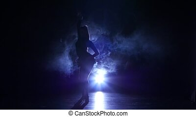 Girl is dancing in smoke latin dance. Dark background, blue backlight