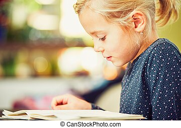 Girl is doing homework - Little girl with school book is...
