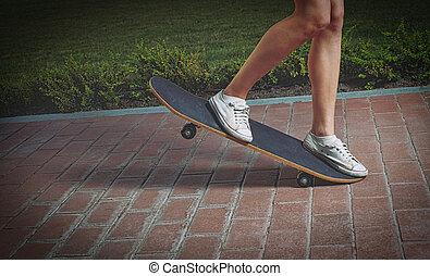 Girl is doing skateboard trick on the park lane