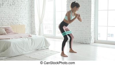Young woman is doing squats for glutes using stretching strap for workout and training at home. Sporty fit girl is making fitness aerobic exercises in bedroom. Home fitness and wellness concept.