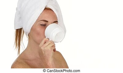 girl is drinking coffee. she has towel on her head. slow motion