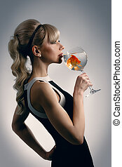 Girl is drinking glass of water with golden fish
