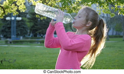 girl is drinking water from the bottle - Little girl is...