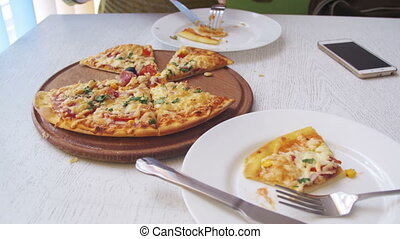 Girl is Eating Pizza in a Cafe with a Mobile Phone on a White Stylish Wooden Table