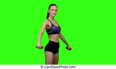 Girl is engaged with dumbbells. Slow motion. Green screen