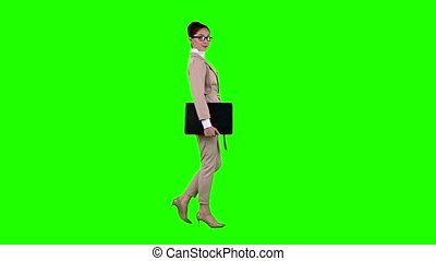 Girl is going to a meeting with a laptop in her hands. Green screen. Side view. Slow motion