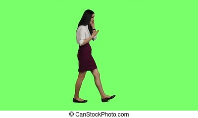 Girl is going to an important meeting, talking on the phone, she is angry. Green screen. Slow motion