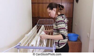 Girl is hanging laundry on dryer - On tumble-dryer brunette...