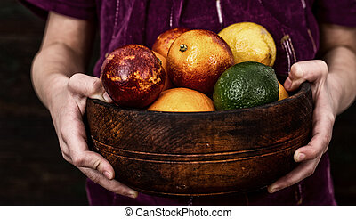 Girl is holding a bowl of citrus fruit
